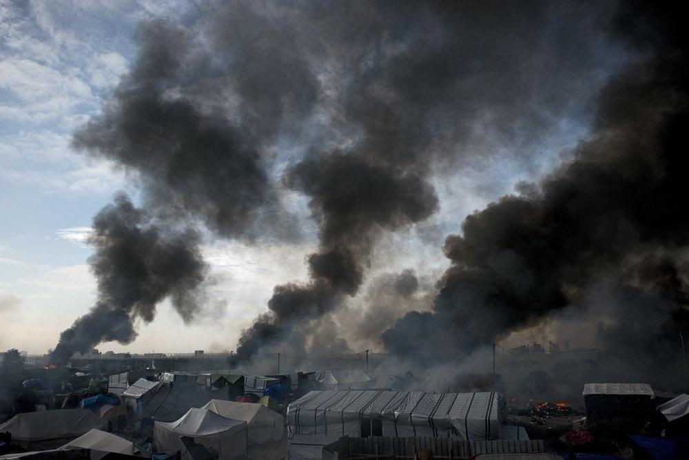 Calais, mercredi 27 octobre 2016. Dans la matinée du troisième jour de l'opération de démembrement, le bidonville s'enflamme. Des volontaires de l'Auberge des migrants tenteront en vain de circonscrire les premiers incendies avec des moyens de fortune. Sur une butte au milieu du camp, les journalistes et les CRS observent, médusés, des pans entiers du bidonville disparaître dans les flammes. Une bénévole britannique arrive, complètement essoufflée. Elle pointe du doigt un coin du campement. « Ils sont là, je viens de les voir mettre le feu. » Ce n'étaient pas des migrants, mais « de jeunes Français ».