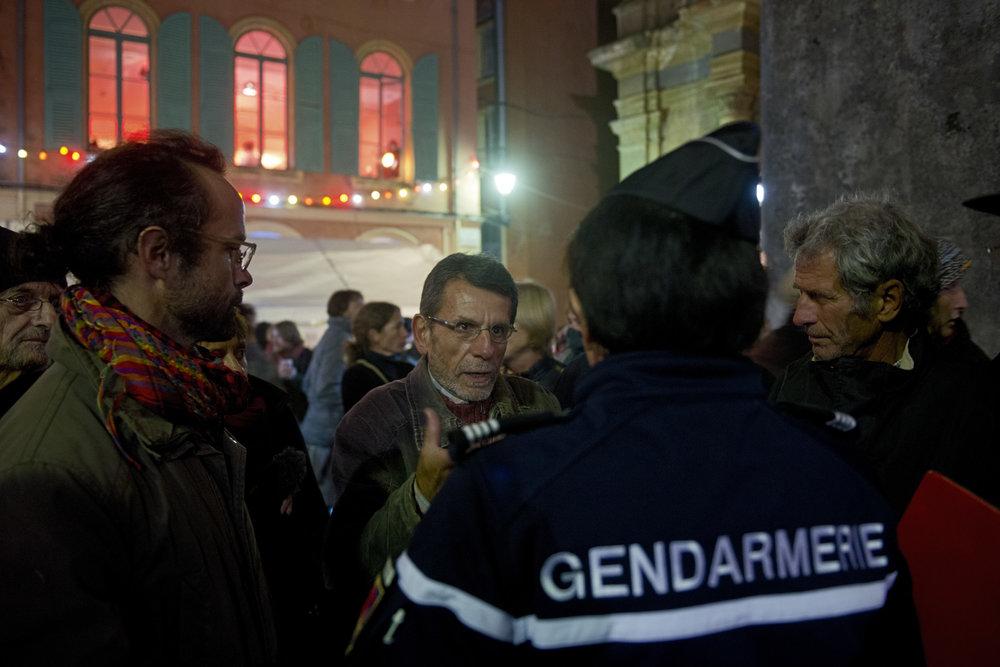 L'agriculteur Cédric Herrou accompagné d'un membre du conseil municipal, Gilbert Cottalorda, et d'un membre de l'association Roya Citoyenne tentent de négocier l'ouverture d'une salle municipale pour pouvoir abriter les migrants pour la nuit.