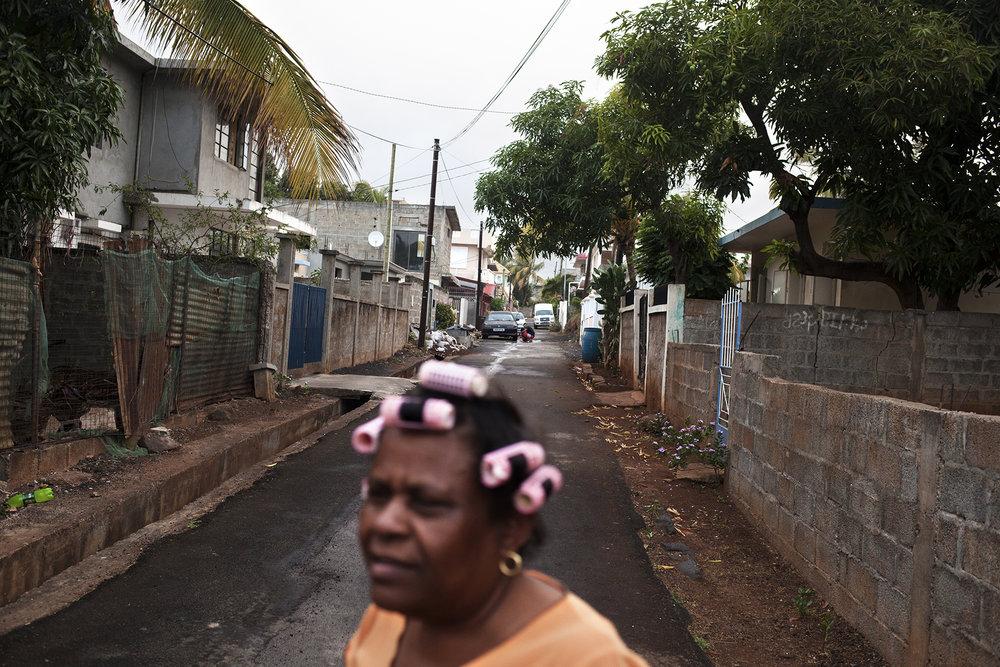 Miroze a quitté les Chagos pour la dernière fois en 1968 avec son petit frère, Olivier Bancoult, dirigeant du Chagos Refugee Group. Depuis elle vit dans le quartier de Pointe aux Sables, non loin de sa maman. Mais loin de ses enfants. Cinq d'entre eux sont en Angleterre. « Il y a beaucoup de problèmes de racisme avec les indous ici à Maurice… en Angleterre non, et il y a du travail. C'est pour ça que mes enfants sont partis » L'eau monte à ses yeux et Miroze prend appui sur la commode où trônent des portrais de ses enfants, de Jésus et du pape Jean Paul II pour ne pas sombrer. Elle a perdu son île il y a plus de quarante ans, maintenant elle perd sa famille, toujours plus rejetée, toujours plus loin.