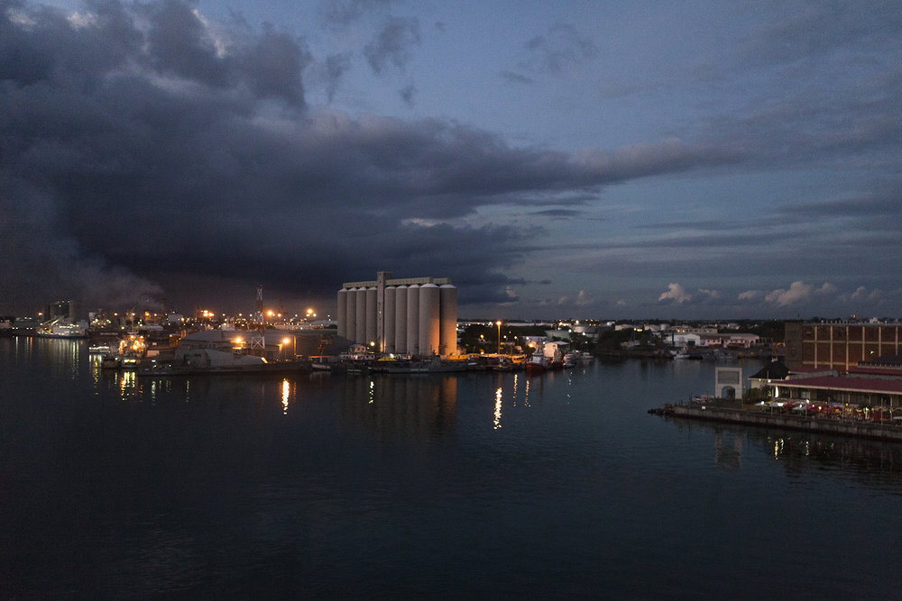 La baie de Port Louis, capitale de l'Ile Maurice. La principale ouverture maritime vers ces ailleurs.C'est ici que transitent tous les bateaux reliant ce petit bout de l'indien au reste du globe.Une plate forme commerciale colossale entre l'Asie et l'Afrique.A l'époque les bateaux reliaient Maurice aux Chagos régulièrement.Puis en 1965 tout s'est arrêté.Brusquement. Sans les prévenir.« Ce n'est plus votre île, vous ne repartez pas. »Les Chagos avaient été vendu aux Anglais puis loué aux Américains pour y établir leur principale base militaire de l'Océan Indien.Une histoire de commerce mondial.Une histoire de stratégie et de géopolitique.Une histoire humaine. Tragiquement humaine.