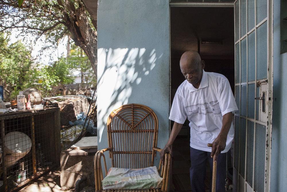 Raymond Antalika a 102 ans. Un siècle passé.Son père et sa mère sont nés au Chagos. Lui est né et a grandi à Maurice où il était ébéniste.Ses petits enfants qui s'occupent de lui chaque jour ne connaissent pas l'histoire des Chagos.Ils ne savaient même pas avant notre venue que leurs arrières grands parents étaient Chagossiens.Tout cela est très loin d'eux et de leur quotidien.Le temps a fait son affaire.Tout cela fait sourire Raymond. Lui est mauricien. Sa vie a lui est ici, dans ce quartier de Roche bois. Dans cette maison qu'il ne quitte plus. Naviguant péniblement entre son lit et sa petite terrasse où trône son fauteuil fétiche. « Je ne sais pas pourquoi mes parents sont venus à l'île Maurice. Ehé.»Raymond est heureux d'avoir de la compagnie aujourd'hui. « Vous restez boire une bière ? » Une grande bouteille de Phénix. Pour renaître encore un peu. Comme chaque jour. Et garder le sourire.