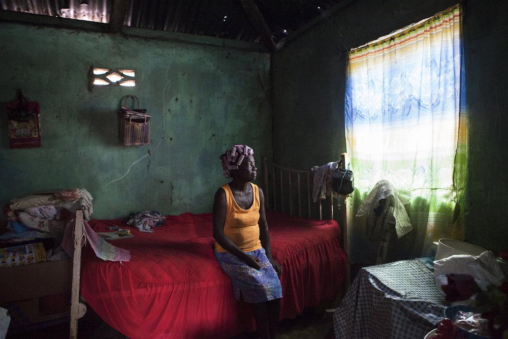Personne fait rien pour band' Chagossiens ! Et puis quoi faire contre band' Zaméricains ! Nou la ziste la misèr'… Rosemay parle vite et fort, elle harangue, elle rit, elle vocifère puis vous regarde avec ses yeux rieurs. Assise fièrement devant l'amât de tôle protégeant sa case misère, Rosemay se charge d'animer la rue. Une jeune fille enceinte se tient à ses côtés sur le bord de route, elle a 14 ans. Rosemay elle en a 67. Elle en a vu d'autres.Nous suivons Rosemay chez elle. Dans cette parcelle qu'elle partage avec d'autre familles. Elle, vit seule. Chien mauvais nous accueille en nous mordant les mollets. Un autre s'excite derrière une rambarde en tôle.  Nous la suivons dans un dédale de tôles enchevêtrées les unes sur les autres, faisant office de case dont l'intérieur est usé par le temps qui passe, inlassablement. Rosemay est née à Perros Banhos, a été déportée comme les autres Chagossiens, s'est mariée à un mauricien, mort depuis. Là bas plus beau qu'ici, cent pour cent, ah !Rosemay fume fièrement ses clopes, gardant longtemps la fumée en elle avant de l'extirper dans un puissant nuage blanchâtre. Nous lui faisons prendre la pose pour tirer son portrait. Vous me trouvez belle ? Ah ! je suis vieille oui !Rosemay vit de sa maigre pension. Personne ne l'aide. Ses enfants ne l'aident pas non plus. Olivier Bancoult ne l'aide pas non plus. « Volèr sa ! Tout pour lui et sa famille ! Belle maison, voyages et nou quoi ? La misèr ! La misèr ! »Une dernière bouffée sur sa cigarette et un sourire en coin en guise d'aurevoir.« Vous revenez demain ? »