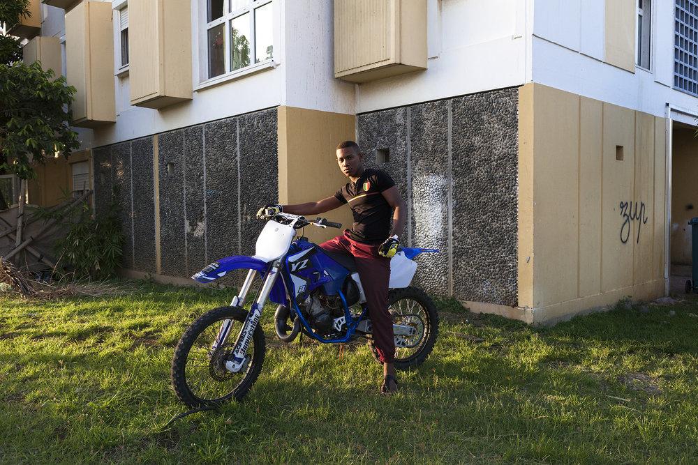 Portrait d'un jeune sur sa moto devant son immeuble. Les jeunes de la ville du port comme dans l'ensemble de l'île de La Réunion vouent une grande passion pour les motos et les voitures tuning. Le Port est réputé dans toute l'île pour ses défilés de motos chaque année au moment de Noël et nouvel an. Des défilés souvent illégaux mais qui sont une tradition festive dans cette ville.