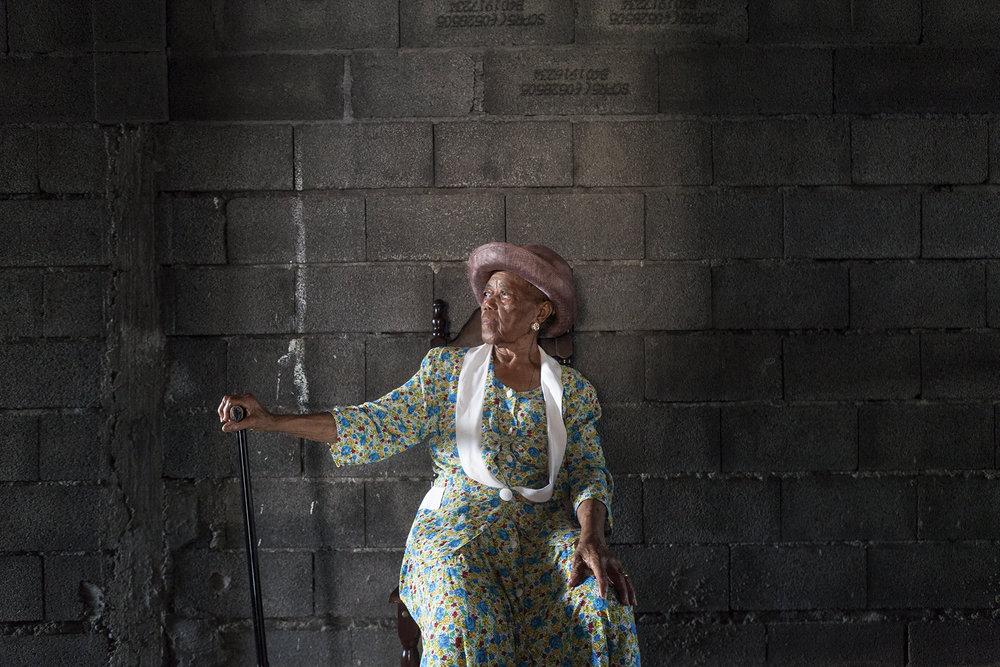 Augustine est âgée de 88 ans. Elle a travaillé pendant de nombreuses années dans les bureaux de la douane où elle y faisait le ménage. Son mari, décédé à l'âge de 45 ans travaillait comme mécanicien dans les chemins de fer, puis comme docker. Augustine est née au Port et y a toujours vécu.