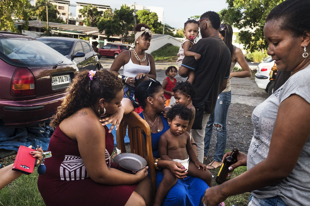 Vendredi après-midi durant les vacances scolaires. Une fête d'anniversaire est organisée pour des enfants dans le quartier de la ZAC 1. Les parents et les marmailles investissent le trottoir, pour profiter de ce moment de convivialité.