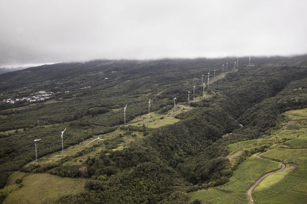 Vue aérienne de la ferme éolienne de La Perrière. Ces bipales s'élèvent à 55 mètres du sol pour 32 mètres de diamètre. Leur implantation sur ce site du nord de l'île de la Réunion, sur la commune de Sainte-Suzanne, s'est faite en trois tranches, entre 2005 et 2007. Avec raccordement au réseau EDF au fur et à mesure. Juillet 2015, Ile de la Réunion.