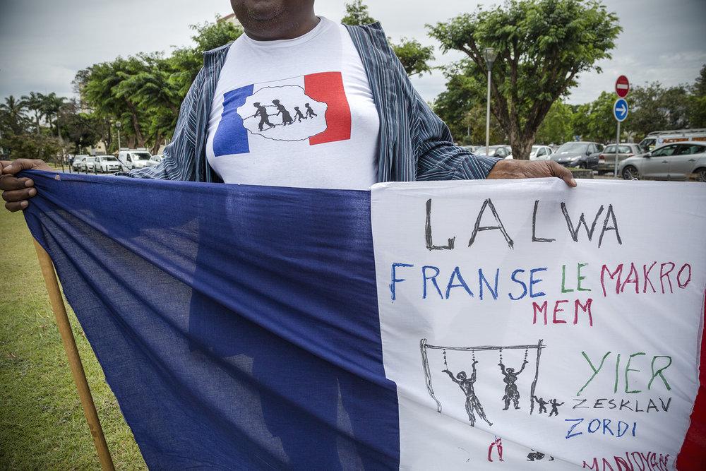 Novembre 2015, Tribunal de Saint-Denis. Un militant de l'association Eveil Citoyens 974 brandit un drapeau tricolore avec l'inscription « La loi française est corrompue.  Hier esclaves, aujourd'hui mendiants ».  Cette association suit plus de 300 dossiers qui  traitent de cas de spoliation de terrain dans le domaine public ou privé, mais aussi des affaires d'abus de pouvoir ou de corruption.