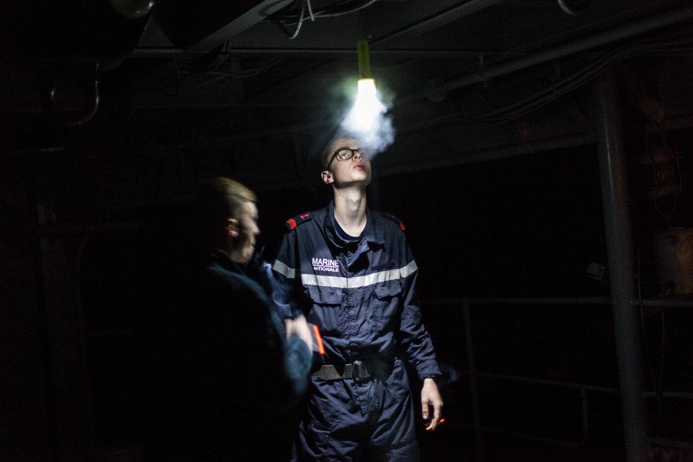 """Mer méditerrannée, 01.12.2015. Pause cigarette pour un membre de l'équipage, sur la plage arrière de la frégate le """"Jean Bart"""", lors d'exercices interarmées en Méditerrannée."""