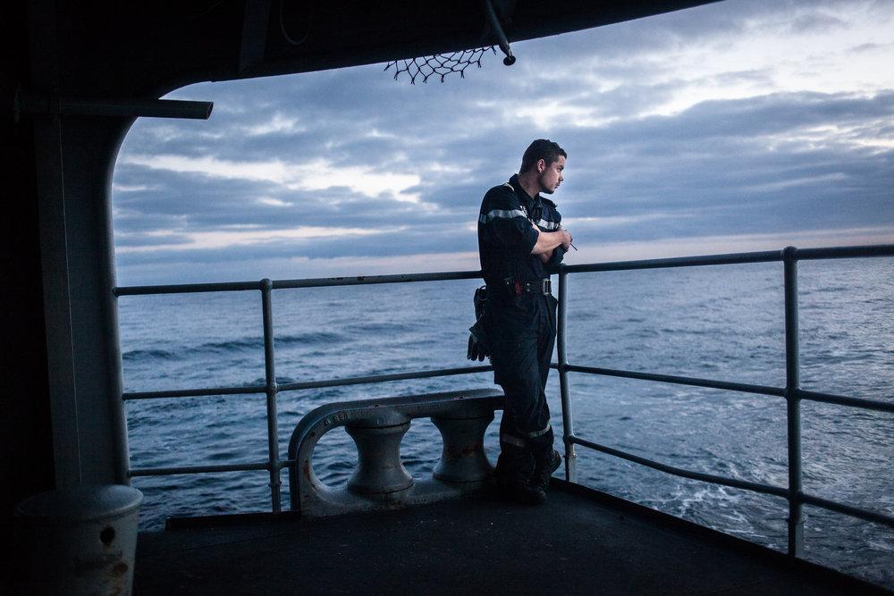"""Mer méditerrannée, 02.12.2015. Pause cigarette pour un membre de l'équipage, sur la plage arrière de la frégate le """"Jean Bart"""", lors d'exercices interarmées en Méditerrannée."""
