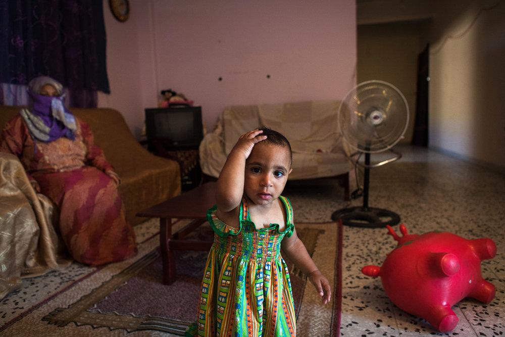 """Tripoli, 27 Juin 2012. Bab-al-Azizia, ancien bastion de Kadhafi au centre de Tripoli. Des familles démunies occupent les ruines de la place forte, devenue depuis un haut lieu de traffic (drogues, alcool, prostitution...). Cette femme dont le mari est très souvent absent doit s'occuper seule de sa fille handicapée. Un soir, elle sort de chez elle pour demander aux prostituées d'aller plus loin et d'arrêter le tapin. La nuit même, la façade de leur """"appartement"""" est mitraillé par les milices organisant les trafics dans le complexe. Face aux menaces, elle se dit prête à se battre pour protéger sa famille.Tripoli, June 27, 2012. Bab al-Azizia, Gaddafi's former stronghold in central Tripoli. Poor families occupy the ruins of the fortress, which has since become a mecca for traffic (drugs, alcohol, prostitution ...). The woman whose husband is often absent, must take care of her disabled daughter alone. One night she came out the door to ask prostitutes to go further and stop the hustler. The same night, the facade of their """"apartment"""" was shot by the militia organizing traffic in the complex. Face of threats, she is willing to fight to protect her family."""