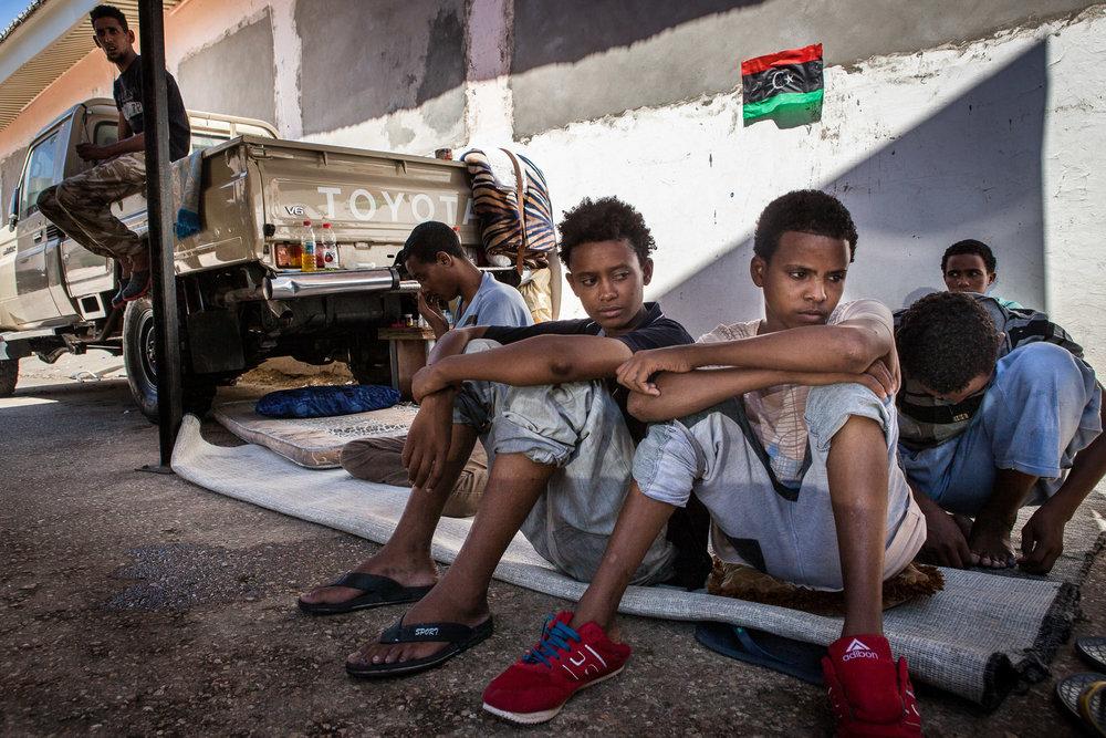Tripoli, le 8 Juillet 2015. Mineurs isolés erythréens vivant dans le Centre de détention pour migrants illégaux dans le quartier général du département de lutte contre la migration illégale. Le gouvernement de Fajr Libya, installé à Tripoli, est en recherche de reconnaissance de la part de la communauté internationale. Conscients que les conditions de vie dans les camps sont difficiles, ils demandent de l'aide financière et logistique à l'occident pour réussir à gérer la migration illégale transitant par son territoire. En attendant, les migrants illégaux sont entassés dans des lieux insalubres, sans possibilité de sortir ni d'avoir suffisamment accès aux soins.Tripoli, July 8, 2015. Eritrean migrant children  in the Detention Center, the headquarters of the Department of fight against illegal migration. The government of Fajr Libya, based in Tripoli, is looking for recognition from the international community. Aware that the living conditions in the camps are difficult, they ask for financial and logistical assistance to the West to successfully manage illegal migration transiting through its territory. Meanwhile, illegal migrants are crammed in unhealthy places, not allowed to go out or to have sufficient access to care.