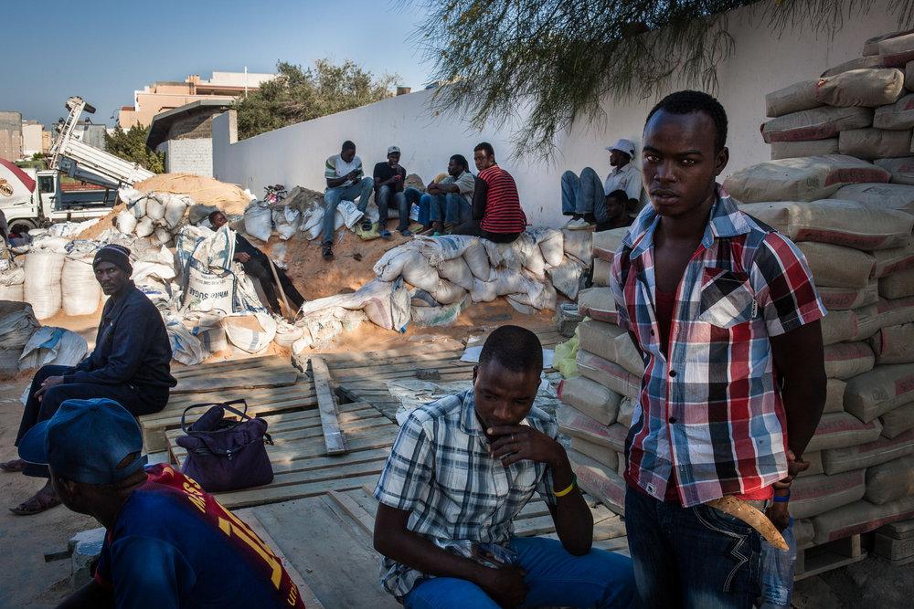 Tripoli, le 8 Juillet 2015. Dans certains quartiers de Tripoli, des migrants illégaux proposent leurs services sur le bord de la route. Maçons, peintres, électriciens, certains cherchent à gagner de l'argent pour envoyer à leur famille restée au pays, d'autres cherchent à accumuler de quoi payer le passage vers l'Europe. Tous s'accordent à dire que ces derniers mois, il y a de moins en moins de travail, et que les salaires ont été sérieusement réduits. Ils sont régulièrement victimes d'arnaques, de racket, voire d'enlèvements.Tripoli, July 8, 2015. In some neighborhoods of Tripoli, illegal migrants are offering their services on the roadside. Masons, painters, electricians, some seek to earn money to send to their families back home, others are looking to accumulate money to pay the passage to Europe. All agree that in recent months, there is less and less work, and wages have been seriously reduced. They are regularly victims of scams, racketeering and even kidnappings.