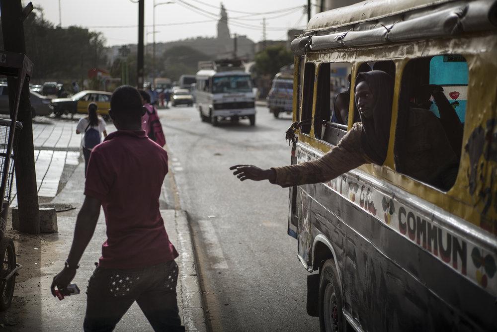 Circulation routière à Dakar, Sénégal. Mai 2017Un usager appelle un marchand ambulant pour acheter de l'eau, des cigarettes, des insecticides, etc. Quartier de Ouakam.