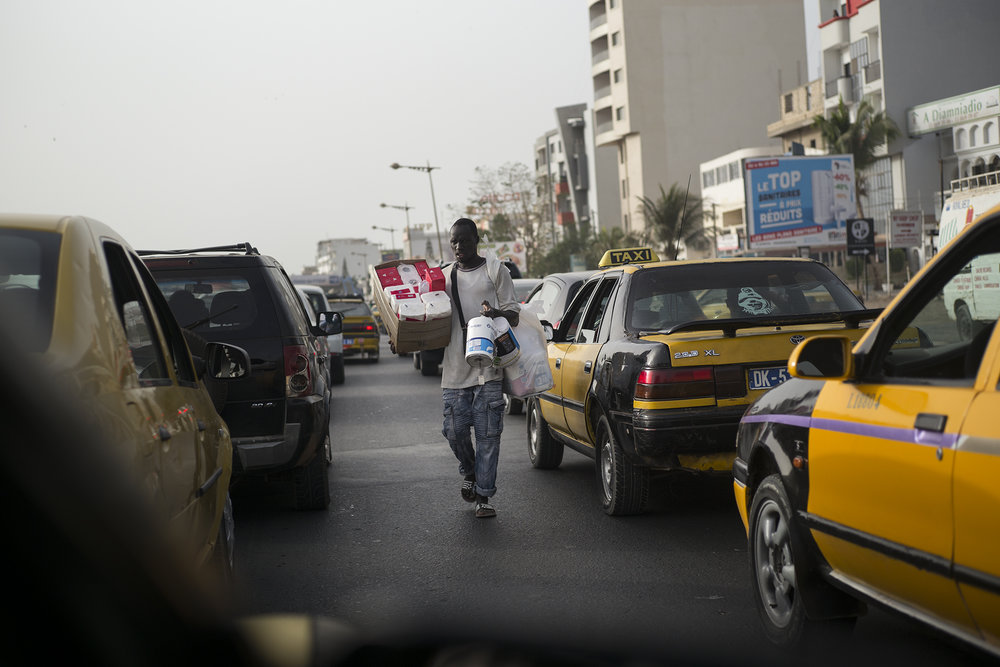 Circulation routière à Dakar, Sénégal. Mai 2017Un vendeur déambule entre les véhicules lors des heures de pointes. Centre-ville de Dakar.