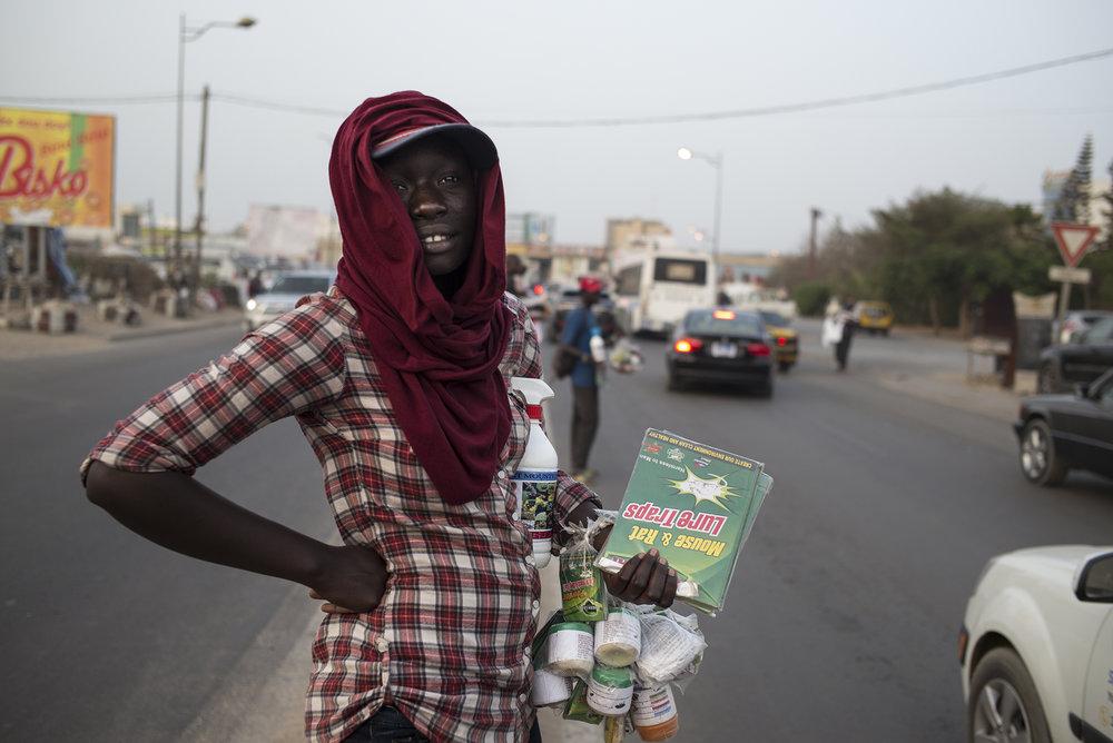Circulation routière à Dakar, Sénégal. Mai 2017Coumba Diouf profite des embouteillages pour écouler son stock d'insecticide. cette jeune femme de 24 ans partage ses journées entre un travail d'aide ménagère et la rue.