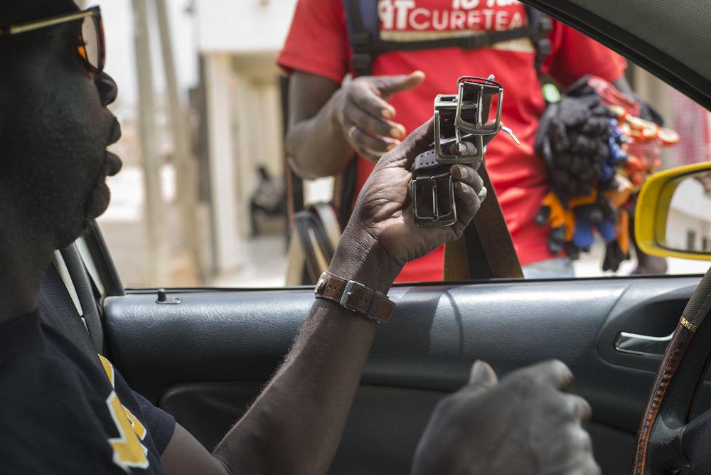 Circulation routière à Dakar, Sénégal. Mai 2017Un chauffeur de taxi en négociation avec un vendeur de rue.