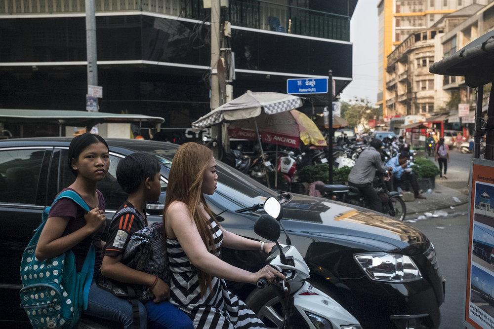 """Mars 2016. Scène de rue dans le centre-ville de Phnom-Penh.En jetant la population des centres urbains sur les routes, les Khmers rouges exécutent leur plan de ruralisation forcée. La moitié des Cambodgiens vont ainsi se retrouver dans les rizières, pour y être """"rééduqués"""". Un quart d'entre eux y trouveront la mort et les autres fuieront."""