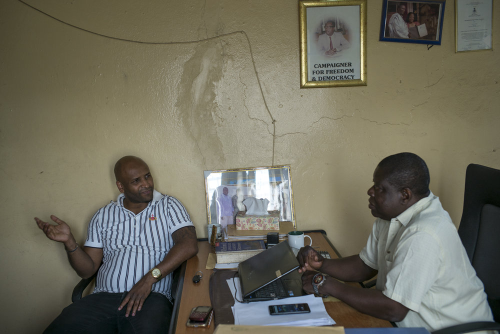 """""""The Point"""" newspaper. Bakau district, Serrekunda, Gambia. January 2018Baba Hydara is chatting with the administrator of the newspaper. On the wall, a portrait of his father with the slogan """"Campaign for Democracy"""". At 42, the journalist and editor of the newspaper """"The Point"""", Baba Hydara is back after 13 years of exile in the US and UK. His wish is to change press environment and reconnect with the investigation. Baba is the son of Dayda Hydara, the former dean of the Gambian press and co-founder of The Point newspaper. Dayda Hydara was murdered on December 16, 2004. His killers remain unpunished to this date."""