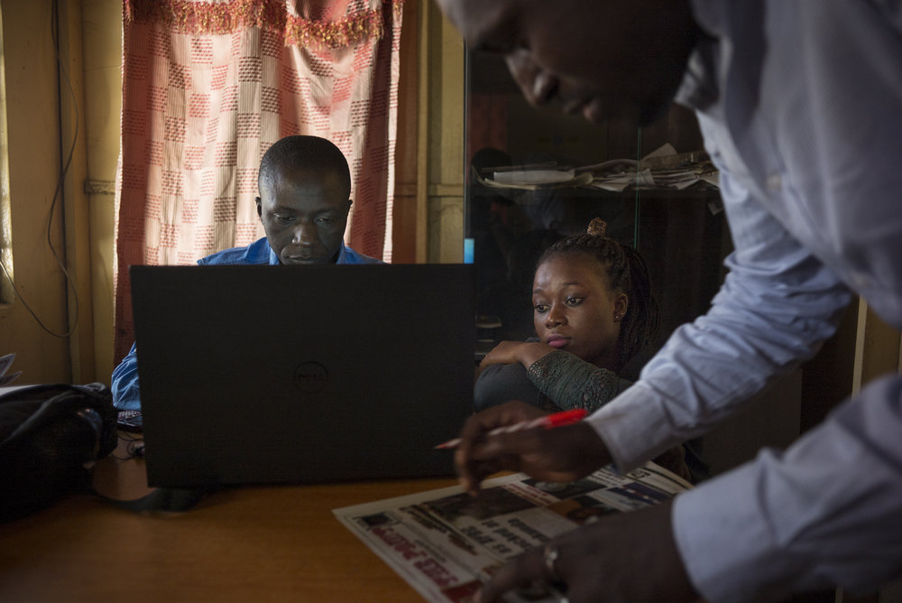 """""""The Point"""" newspaper. Bakau district, Serrekunda, Gambia. January 2018In his office, the news editor revises a report with Fatou, a young journalist recruited less than a year ago at """"The Point"""". As in other media, the recruitment of new journalists is becoming more and more important with the return of the freedom of speech."""