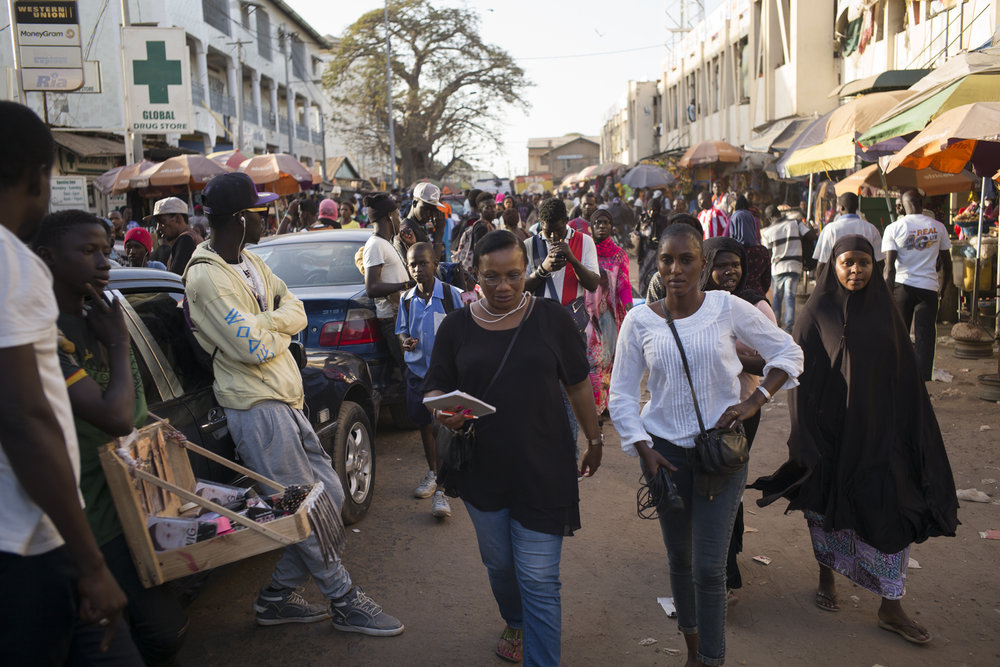 """Fatu Jaw Manneh and his journalist in Serrekunda market, Gambia. January 2018QTV's editorial director, Fatu Jaw Manneh (left) is supervising a reportage with his reporter in the Serrekunda market. QTV is the first private television channel in the country. The channel's programs began in February 2018. The television channel is owned by the telephone operator Qcell.Fatu Jaw Manneh worked in the newspaper """"The Daily Observer"""". As an opponent of Jammeh's regime, she had to flee quickly after his Coup d'État. She had been persecuted and threatened. Beyond borders, she has always remained a human rights activist for her country. She recently returned to the Gambia after 20 years of exile in the United States."""
