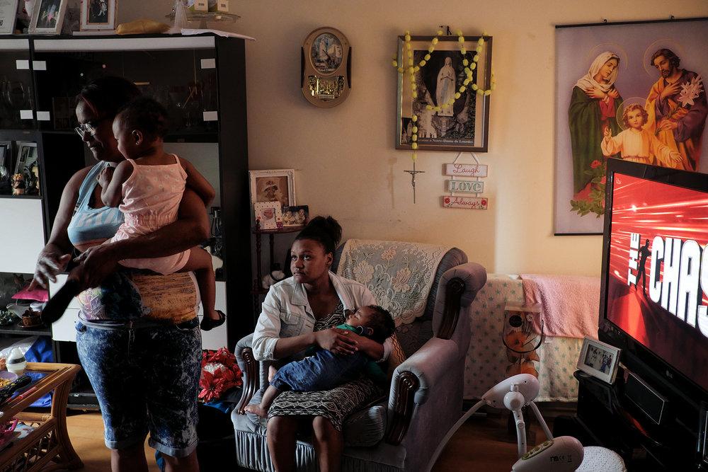 29 juin 2017, Crawley. Dans sa maison avec un de ses petits-fils, Mylène (à gauche de l'image) est une des filles de Lucie. Sur le Canapé, une des filles de Mylène, Anaïs avec son Fils dans les bras.Mylène est arrivée en 2004 avec un ses frères dans le premier voyage qu'avait organisé Allen. Mylène gérait un restaurant dans un quartier de Port-Louis à L'île Maurice mais elle voulait avoir une vie meilleure pour sa famille. Elle décidé de tout quitter. Elle a vécu seule dans ce pays qu'elle ne connaissait pas durant un an et demi sans son mari et ses enfants. Mylène a beaucoup travaillé en tant que « cleaner » pour payer les billets à sa famille. Aujourd'hui, elle retrouvé son métier d'avant, elle travail dans la restauration.Mylène a pu participer une fois a un voyage pour l'archipel des Chagos en 2010. Elle me dit  que ce voyage « m'a fait plus comprendre ces îles où sont mes racines. »