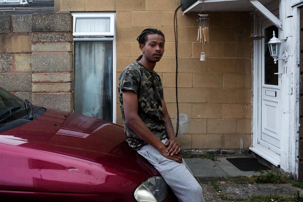 """24 juin 2017. Quartier de Crawley. Stéphane a 25 ans. Il est arrivé avec son papa en Angleterre en 2006. Il travaille aujourd'hui dans le batiment et il pratique la musique comme son père. Il vient d'avoir un petit garçon Julian qui a tout juste 3 mois. Stéphane souhaite lui à l'inverse de nombreux autres jeunes de sa générations retourner sur les Chagos. """"Je voudrais y construire une maison, puis plusieurs pour mon peulpe. Ici, ce n'est pas ma vi, là-bas, il y atout à faire""""."""