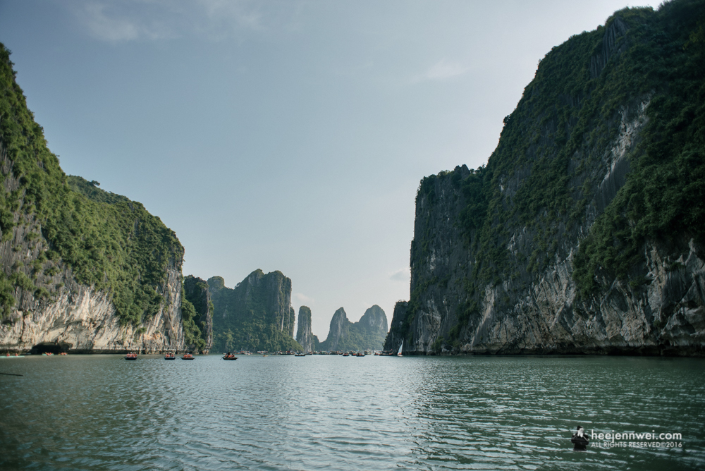 Towering limestone pillars and tiny islets topped by forest rise from emerald waters of the Gulf of Tonkin.