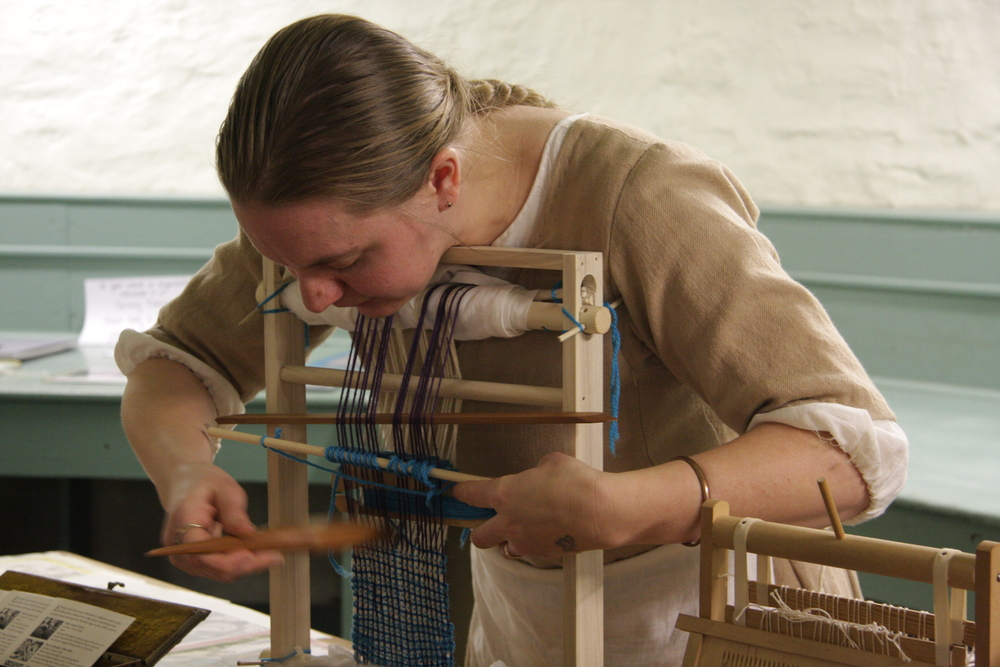 Eva Mergen demonstrates medieval weaving on a scale miniature loom.