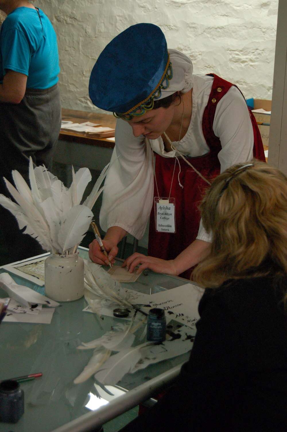 A volunteer helps a visitor try her hand at writing with a quill pen.