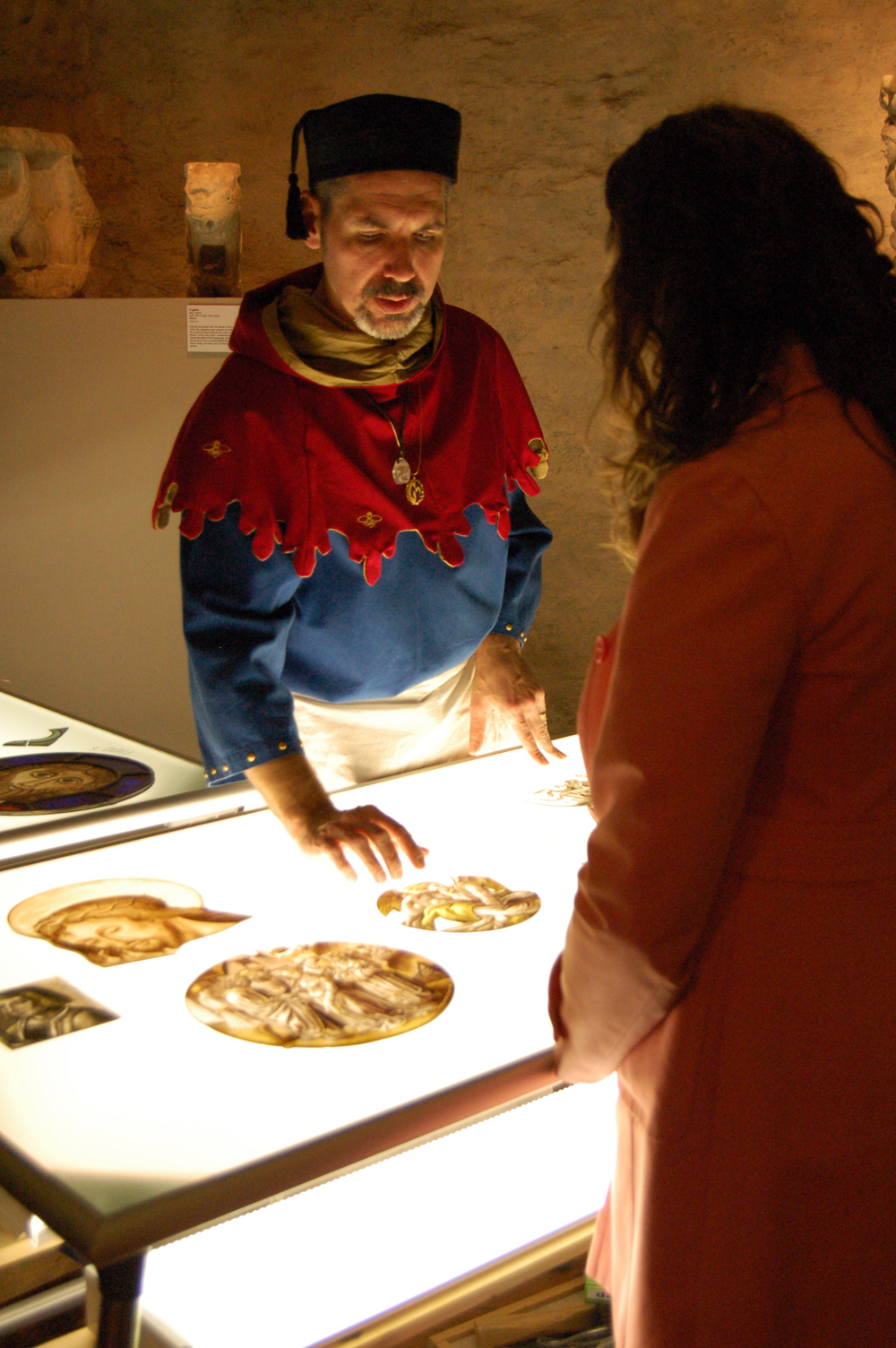 Stained glass artist J. Kenneth Leap talks with a visitor about the art of medieval stained glass painting and window making.