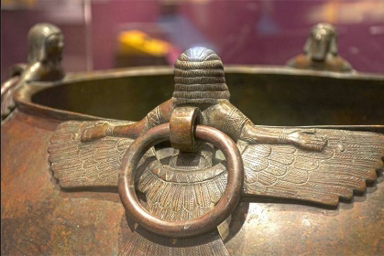 Figure 5:Cauldron from Tumulus MM, Gordion (MM 3), on loan to Penn Museum from the Museum of Anatolian Civilization, Ankara, Turkey, showing back of a bearded demon attachment, with lifting ring intact. Photograph by Ed Gyllenhaal, with permission of Penn Museum.