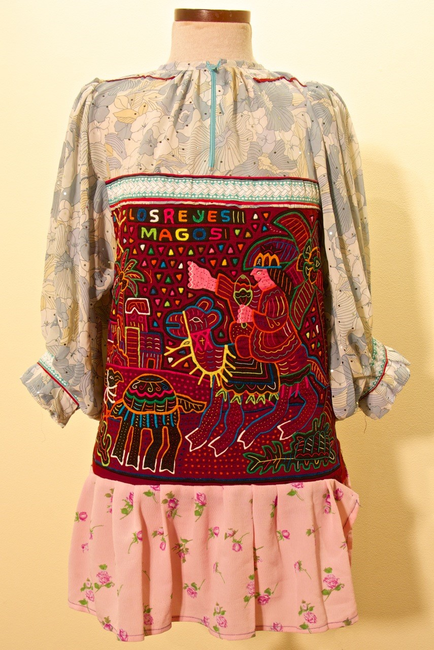 Figure 2: Blouse with Scenes from the Infancy of Christ. Two scenes from the Gospel of Matthew decorate the molas on this blouse. The front panel depicts the journey of the Holy Family during the Flight into Egypt. On the back (pictured here), one of the Wise Men, riding a camel and pointing to the Star of Bethlehem, carries a gift for the baby Jesus.