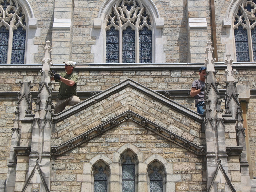 Figure 2: In this photo, three out of four new limestone finials have been set on original bases. Left: Jens Langlotz installs a finial and cleans excess mortar from the base. Right: Grayson Zuber does grouting and cleanup.