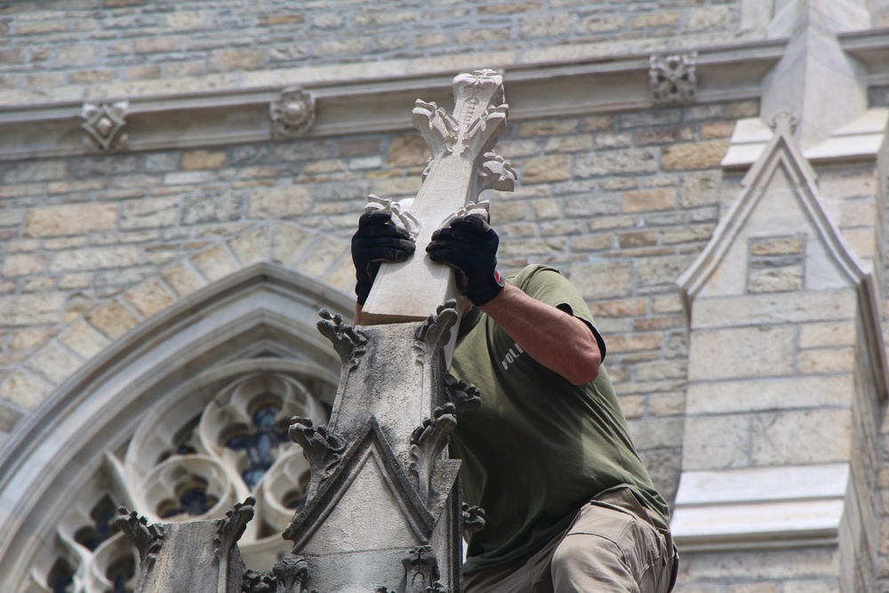 Figure 12: After preparing the base with restoration mortar, Jens Langlotz carefully positions the new limestone finial. The installation of a finial takes just a few minutes, but the carving of a replacement finial takes several weeks.