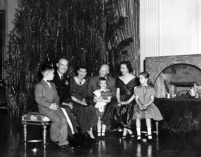 Eisenhower Family in East Room of the White House with Hyatt Nativity |  Winfred S. Hyatt and several craftsmen from Raymond Pitcairn's Bryn Athyn Studios produced the cabinetwork and landscaping, while Hanna Binder, an artist from Bucks County, Pennsylvania, carved the human figures from wood. Photo courtesy of the National Park Service (Abbie Rowe).