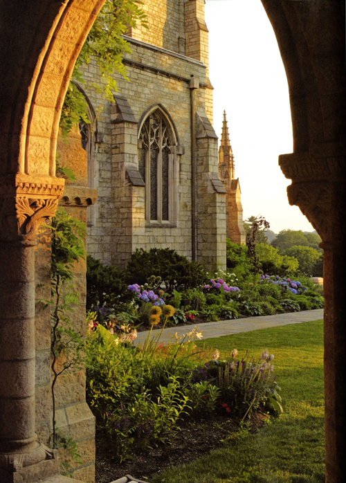 A view of the Cathedral gardens looking out of the cloister arcade toward the corner of the nave (from page 32 of Bryn Athyn Cathedral: The Building of a Church). The west porch is just out of sight. Photograph by Hal Conroy.