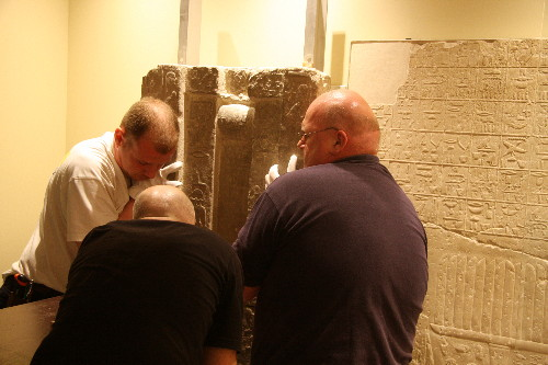 "The installation team lifts the middle portion of Glencairn's spirit door into place beside a relief with Tep-em-ank's ""menu list,"" which is on loan from the Louvre Museum."