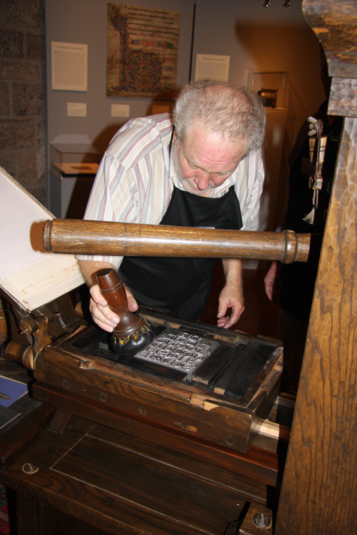 Allen Bjorkman inks the printing plate with a leather ink ball during a demonstration.