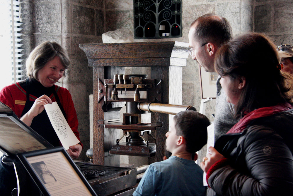 Kirsten Gyllenhaal shows visitors a page she just printed on Glencairn's replica Gutenberg-style printing press.