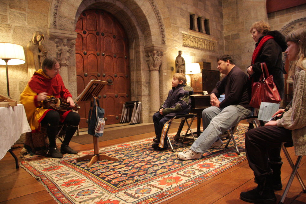 Paul Butler plays a hurdy-gurdy for visitors in the Great Hall.