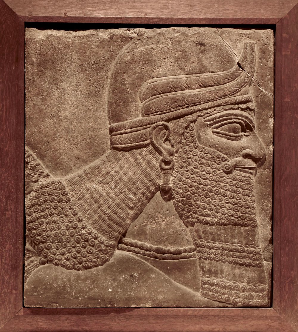 Figure 1: Head and shoulders of a genie, Northwest Palace of Ashurnasirpal II at Nimrud, Iraq. In the 19th and early 20th centuries Assyrian reliefs were often cut down and fitted into a wooden frame to signal their worthiness for purchase or display. (09.SP.1550; 61 x 54 cm)