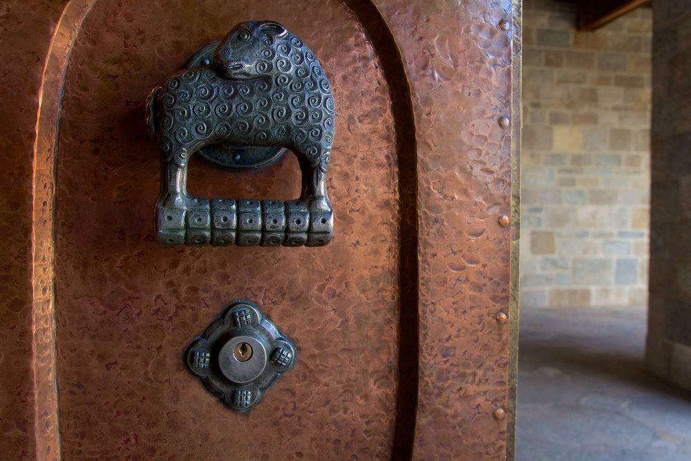 Figure 12: This massive bronze double door leading from the Great Hall to the Cloister features a hand-wrought Monel metal handle on each side. The left handle is a ewe, and the right is a ram.