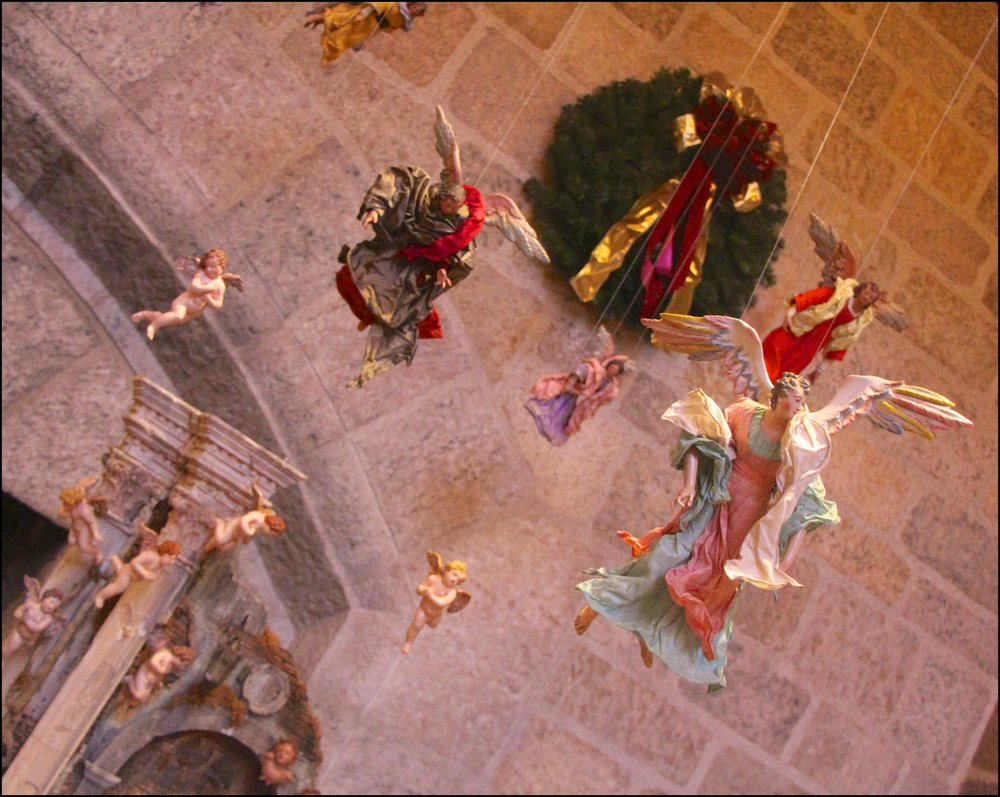 "Figure 16: The angels and cherubs suspended above the Nativity scene may refer to a passage from the Nativity story in the Gospel of Luke: ""And suddenly there was with the angel a multitude of the heavenly host praising God and saying: 'Glory to God in the highest, and on earth peace, goodwill toward men!'"" (2:13-14)."