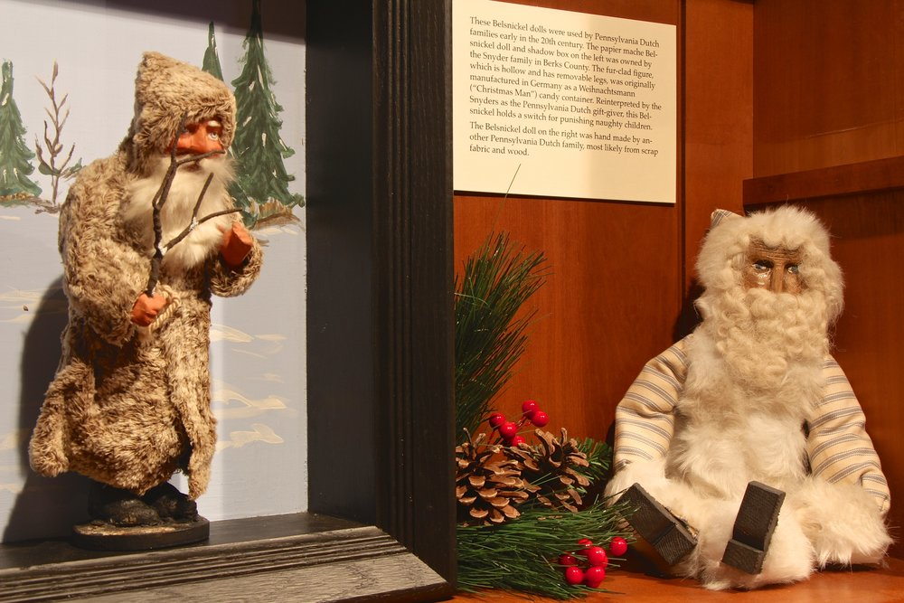 "Figure 3: In Pennsylvania Dutch communities a Christmas gift giver known as Belsnickel made the rounds from farmhouse to farmhouse on Christmas Eve. The name Belsnickel is derived from German and means ""St. Nicholas dressed in fur."" This Pennsylvania Dutch ""Nicholas"" came carrying treats or presents to reward obedient children who could recite a Bible verse or say a prayer. However, Belsnickel was also ready with a rod, switch, or buggy whip to punish any badly behaved children. The Belsnickel dolls pictured here were used by Pennsylvania Dutch families early in the 20th century. On loan from the Pennsylvania German Cultural Heritage Center at Kutztown University."