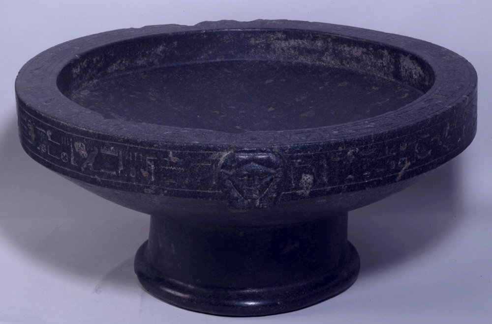 Figure 9: This granodiorite basin of a man named Montuemhet dates to the Late Period.  Hathor heads and a hieroglyphic text decorate the sides. Photo courtesy of the British Museum [EA1292].