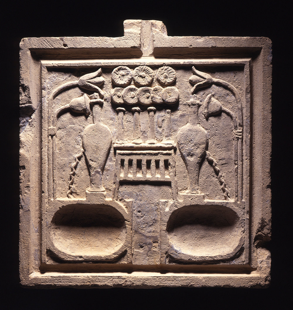 Figure 12: The deceased required food and drink in the afterlife. Offering tables decorated with food, vessels, and sometimes small basins for liquids were a common feature of tomb chapels for much of Egyptian history. This example dates to the Ptolemaic Period and was excavated at the site of Meydum. Photo courtesy of the University of Pennsylvania Museum of Archaeology and Anthropology [UPMAA 32-42-749].