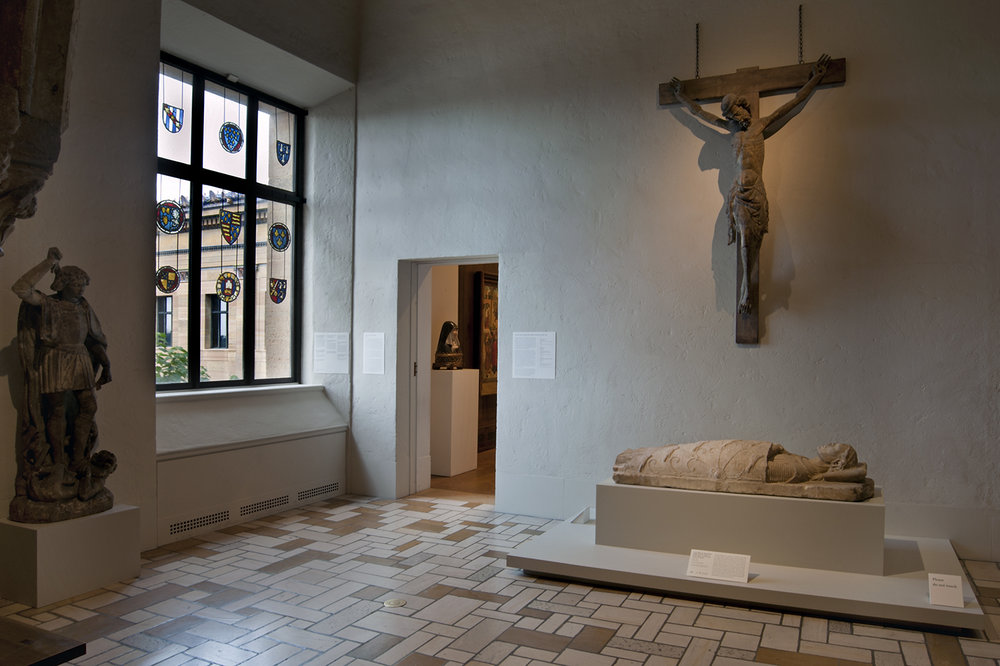 Figure 5: View of a gallery of French Gothic sculpture and English stained glass at the Philadelphia Museum of Art, featuring a Corpus of Christ of the late 13th or early 14th centuries and a Saint Michael Vanquishing the Devil of c. 1500, on long-term loan from Glencairn Museum, alongside the Philadelphia Museum of Art's Tomb Effigy of a Recumbent Knight of c. 1230-40.