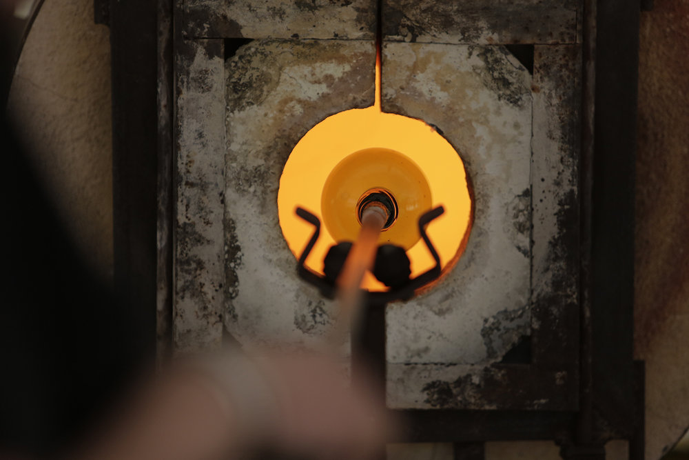 """Figure 1: A gather of glass on the end of the blowpipe sits suspended in the small opening of the furnace. This opening is sometimes called the """"glory hole."""""""