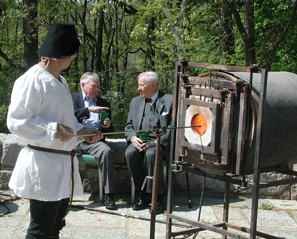 "Figure 4: Jason Klein at the ""glory hole."" To keep the glass hot and workable, it is reheated while still on the blowpipe. In the background, Carl Gunther (left, son of Ariel Gunther, who managed the Bryn Athyn glassworks during its years of operation) and Lachlan Pitcairn (right, son of Raymond Pitcairn) reminisce about the glassworks, which was in continuous operation from July of 1922 to April of 1942. The building was torn down in 1952. Photograph taken in 2006."