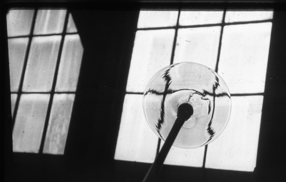 Figure 9: In this archival photograph, a rondel of glass is displayed against the light of a window in the Bryn Athyn glassworks.
